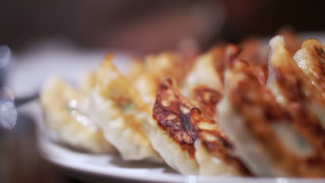 Plate full of delicious Japanese gyoza with one side burnt crust. Eating by chopsticks video