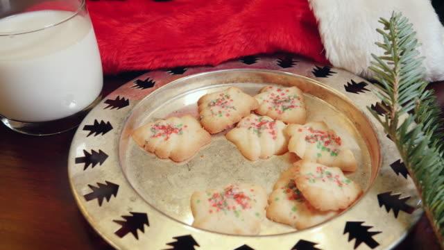 vidéos et rushes de plaque de biscuits de noël et de lait avec un bonnet en 4k - saint nicolas