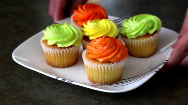 カウンターの上のカラフルな可愛いカップケーキ プレートします。 - カップケーキ点の映像素材/bロール