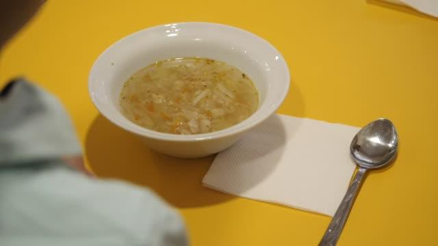 vídeos y material grabado en eventos de stock de frente al niño se coloca un plato de sopa de verduras. - cuenco