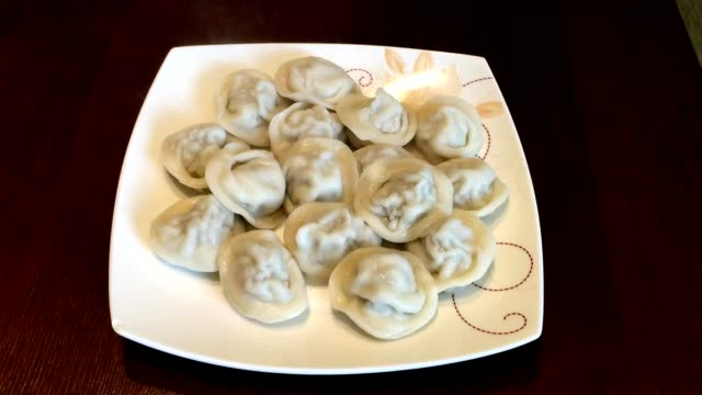 plate with dumplings ravioli. plate of hot homemade dumplings on the table. jet of steam - pentola a vapore video stock e b–roll
