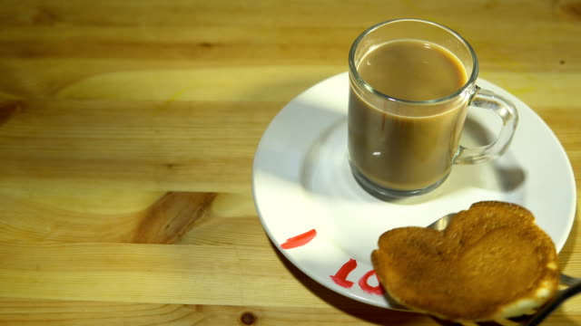 A plate with pancakes in the form of a heart and a mug with coffee on a table. video