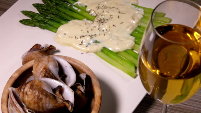 plate with sea snails and asparagus and white wine - cucina francese video stock e b–roll