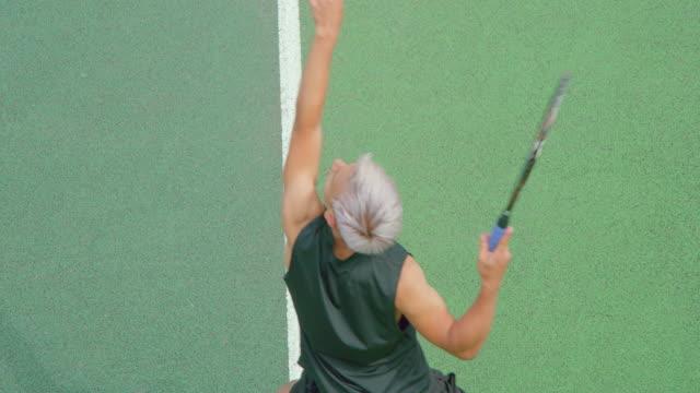 Ein platinhaariger junger erwachsener männlicher Mixed-Renn-Tennisspieler serviert. – Video