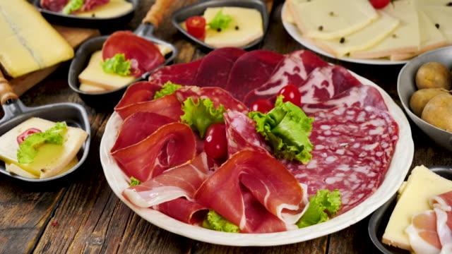 platte mit salami, schinken und raclettekäse - raclette stock-videos und b-roll-filmmaterial