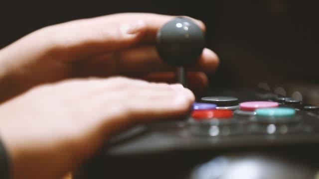 vídeos de stock e filmes b-roll de play with arcade pads to vintage video games - man joystick