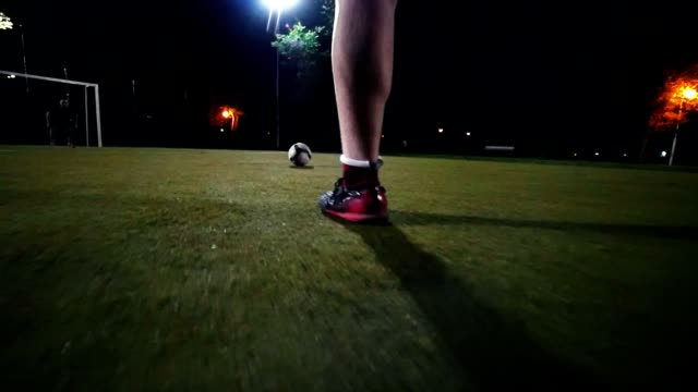 Player in black and red sneakers runs up to the ball and makes a kick towards the goal, but the goalkeeper beats the ball, green grass, night shooting