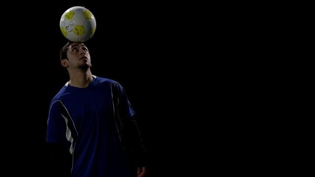 spieler juggles ball auf den kopf und lächeln - geköpft stock-videos und b-roll-filmmaterial
