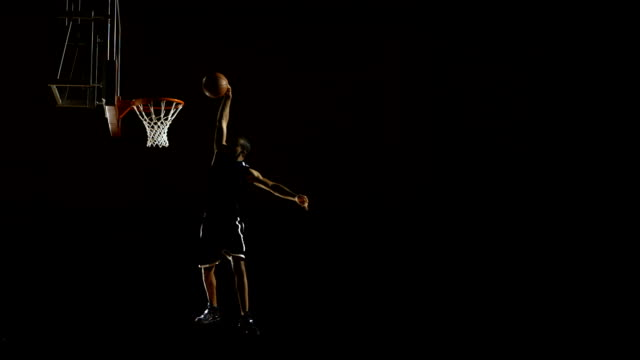 stockvideo's en b-roll-footage met player performing a slam dunk (super slow motion) - basketbal teamsport