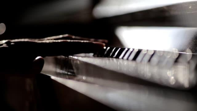 Players hand tounching piano keys and closing keyboard