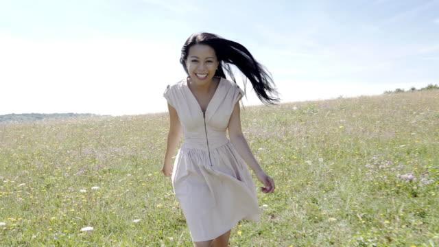 Playful Asian woman running through a meadow. video