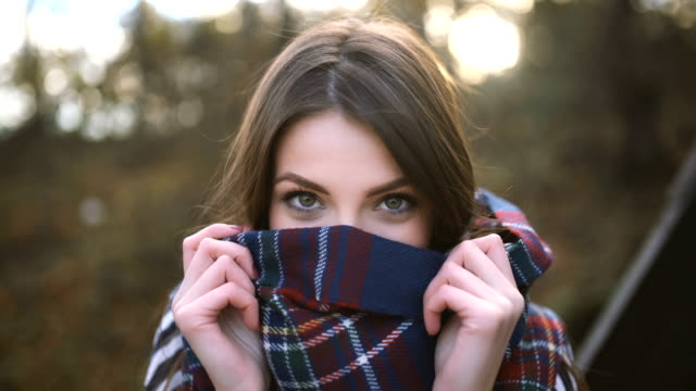 Playful autumn beauty Beautiful, young woman smiling and covering her face with a plaid scarf. hiding stock videos & royalty-free footage