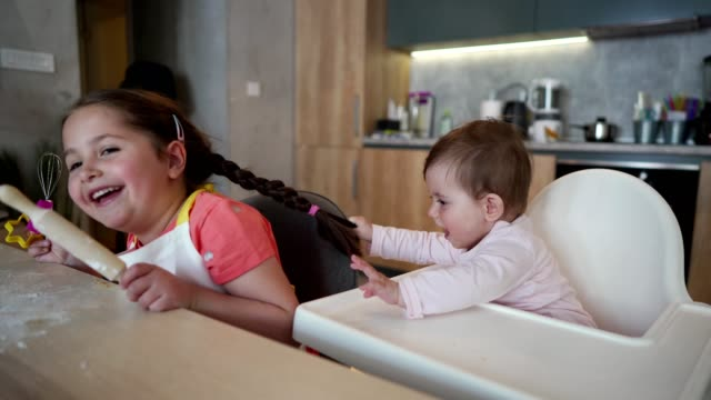 vídeos de stock e filmes b-roll de playful baby girl pulling pigtails her older sister and that makes her laugh - avental