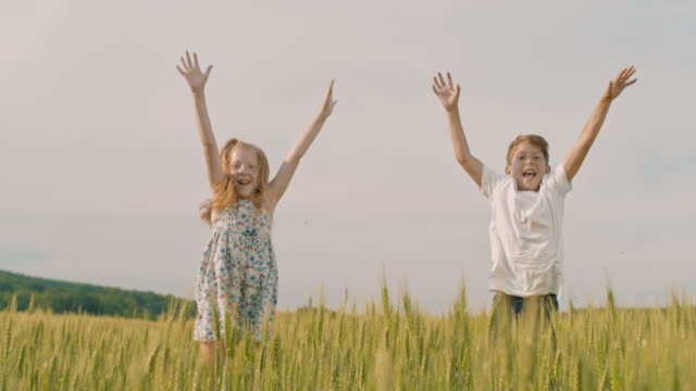 MS Playful boy and girl jumping up from behind wheat in rural field