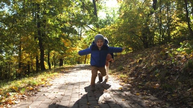 公園で楽しんでいる遊び心のある男の子と特別な女の子 - disabilitycollection点の映像素材/bロール
