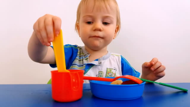 playful child eats fruits and drinking from toy dishes - solo neonati maschi video stock e b–roll