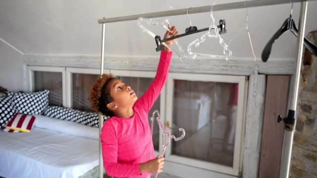 Playful child playing with coathangers at home