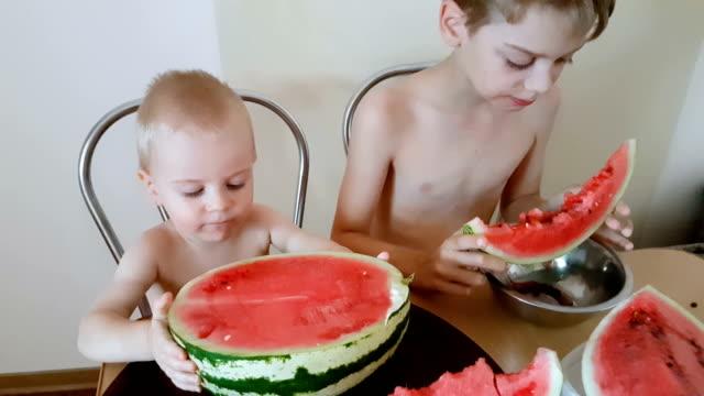 Playful children eating watermelon video