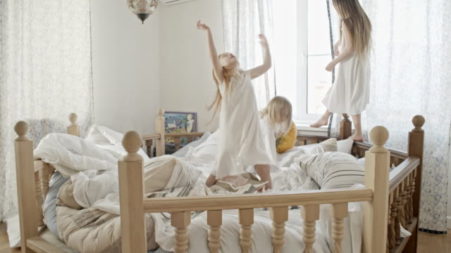 vídeos de stock e filmes b-roll de playful children having fun on bed - sideboard