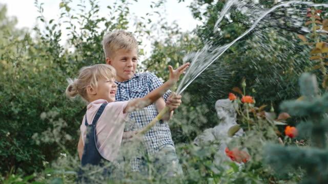 Enfants ludiques d'arrosage de jardin - Vidéo