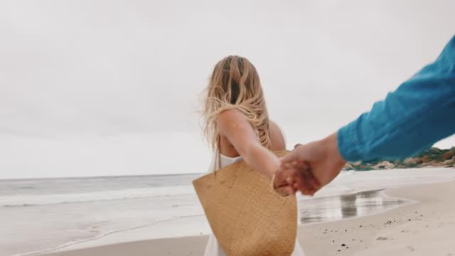 Playful couple enjoying weekend at beach