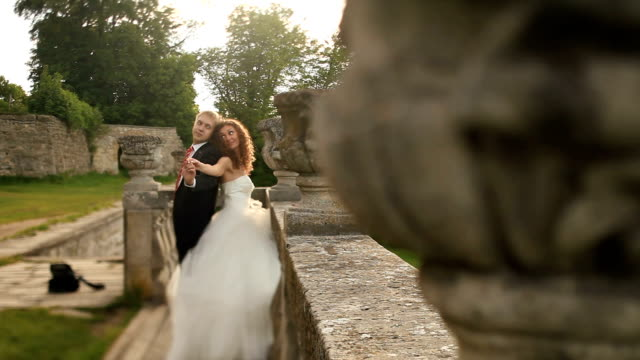 playful couple holding hands together and kisses near old ruined balustrade in park - balaustrata video stock e b–roll