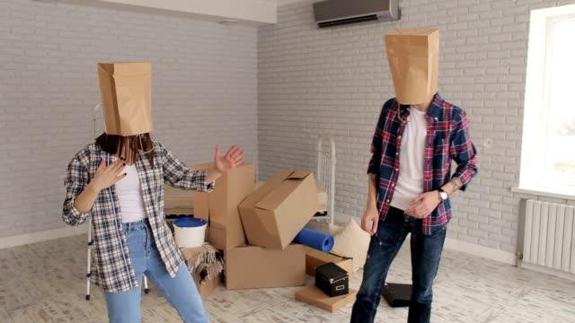 verspieltes paar mit boxen auf kopf, einweihungsparty. - neues zuhause stock-videos und b-roll-filmmaterial