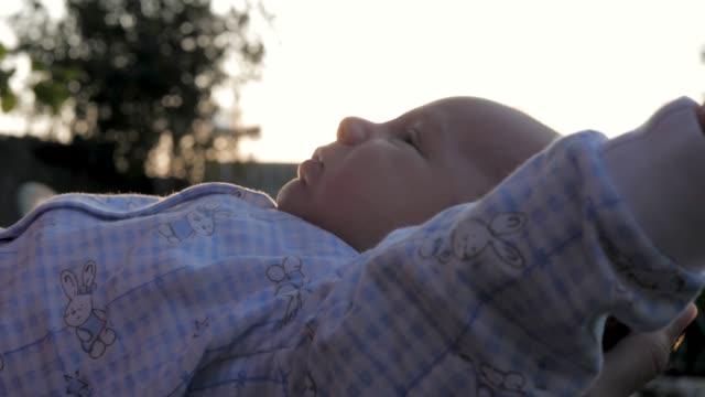 vídeos de stock, filmes e b-roll de bebê fofo brincalhão está deitado nos braços de sua mãe na rua em raios do pôr do sol - braço humano