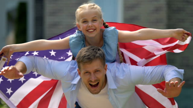 Playful daughter and father with american flag, independence day, celebration Playful daughter and father with american flag, independence day, celebration family 4th of july stock videos & royalty-free footage