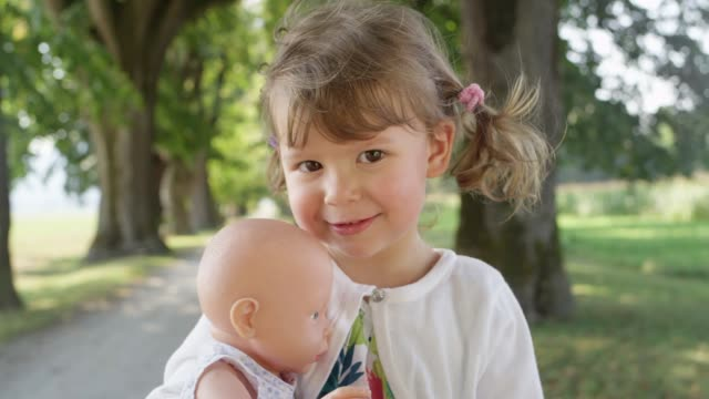 PORTRAIT: Playful daughter smiles for the camera while holding on to her toy. SLOW MOTION, PORTRAIT: Playful daughter smiles for the camera while holding on to her toy. Charming little baby girl stands in the middle of beautiful tree avenue with her favorite plastic toy doll. doll stock videos & royalty-free footage