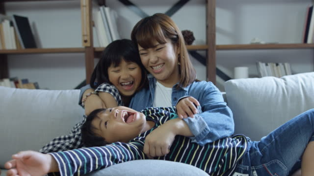 vidéos et rushes de famille ludique embrassant sur canapé - seulement des japonais