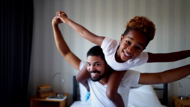 Playful father and daughter having fun in bed Beautiful mixed race family of two, a father and a daughter, having fun in bed in the morning. life balance stock videos & royalty-free footage