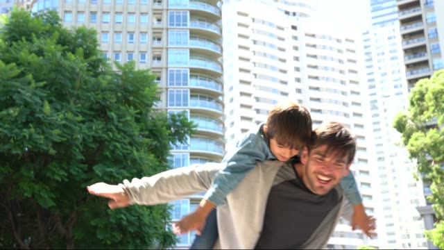 playful father carrying son on back playing like an airplane both smiling - fathers day stock videos and b-roll footage