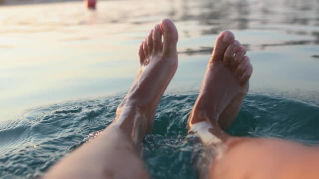 Playful feet in sea water. Young woman enjoying her summer vacation video