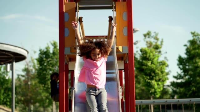 ragazza giocosa in un parco giochi - slitta video stock e b–roll