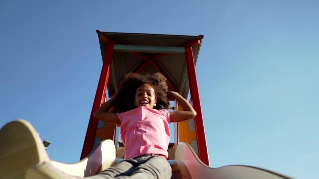 playful girl at a playground - scivolo video stock e b–roll