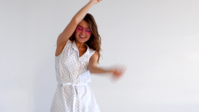 Playful girl dancing while posing against background Close-up of playful girl dancing while posing against background dress stock videos & royalty-free footage