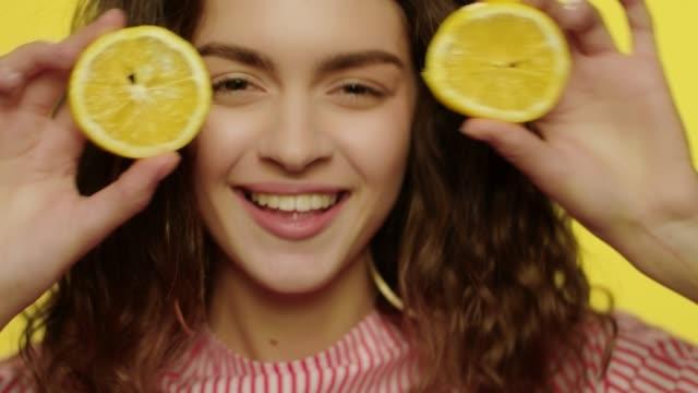vídeos y material grabado en eventos de stock de chica juguetona divirtiéndose con rodajas de limón sobre fondo amarillo. mujer alegre - moda de verano