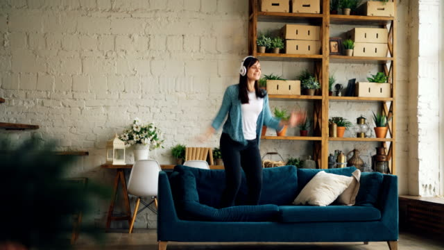 Playful girl is having fun at home listening to music through headphones, dancing on sofa and throwing pillow. Entertainment, people and lifestyle concept.