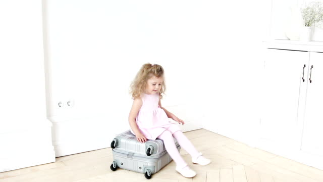 Playful girl sitting on luggage video