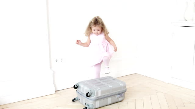 Playful girl standing on luggage video
