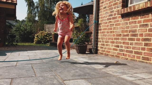 Playful girl using skipping rope in backyard