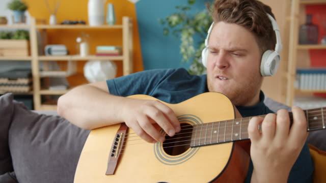 Playful guy playing the guitar at home having fun wearing wireless headphones