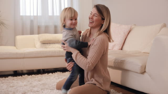 Playful little boy and his mother having fun at home. video