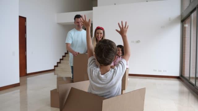 lekfull liten pojke överraskande sin familj genom att hoppa ut ur en kartong medan hans familj packning - flyttlådor bildbanksvideor och videomaterial från bakom kulisserna