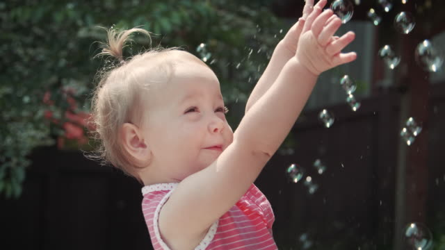 Playful Little Girl Popping Bubbles Outdoors Happy baby playing outside having fun in the sunshine pigtails stock videos & royalty-free footage