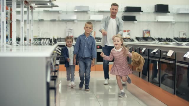 Playful Little Kids Shopping with Dad Playful little kids enjoying shopping with father: family walking together in home appliance store and choosing kitchen stove appliance stock videos & royalty-free footage