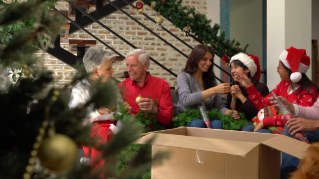Playful loving family having fun decorating with christmas ornaments and wearing props