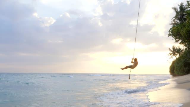 stockvideo's en b-roll-footage met speelse mens die pret met kabelschommel op tropisch strand bij zonsondergang heeft die over het overzees slingert dat hoog in de lucht vliegt. - tarzan