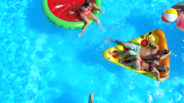 AERIAL: Playful people having fun on inflatable colorful floats in pool water AERIAL: Cheerful friends having water fight on colorful floaties at pool party. Playful guys and girls splashing water and taking selfies on inflatable pizza, doughnut, flamingo and watermelon floats pool party stock videos & royalty-free footage
